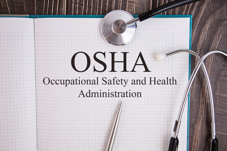 Notebook page with text OSHA Occupational Safety and Health Administration, on a table with a stethoscope and pen, medical concept.